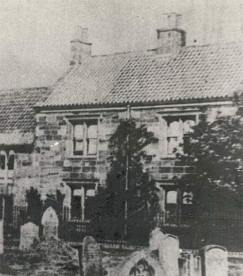 An old photograph of a building which housed the free grammar school in Guisborough until the 1880s. In the foreground are gravestones, as the photograph was taken from St Nicholas' Church yard.