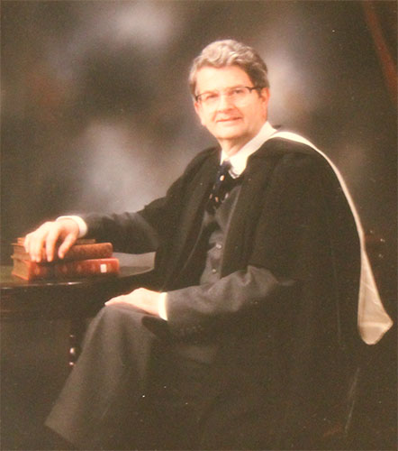 Formal colour photograph of a caucasian male with short wavy greying brown hair and glasses, dresses in a suit and acaemic robes, seated at a table with books.